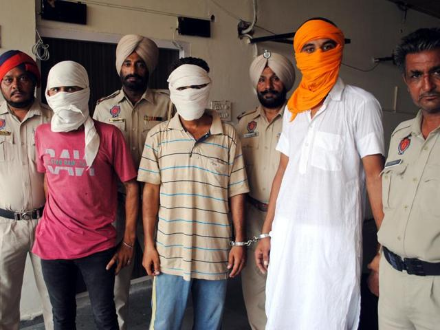 Police with the three accused after a press conference in Bathinda on Saturday.