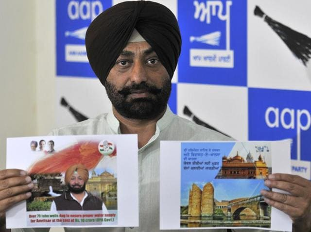 AAP leader Sukhpal Singh Khaira holding the Akali and Congress posters in Chandigarh on Saturday.