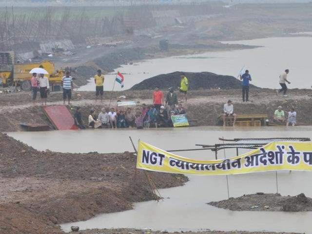 People stand in the Pipliyahana reservoir to protest the decision to construct the court complex, in Indore on Sunday.