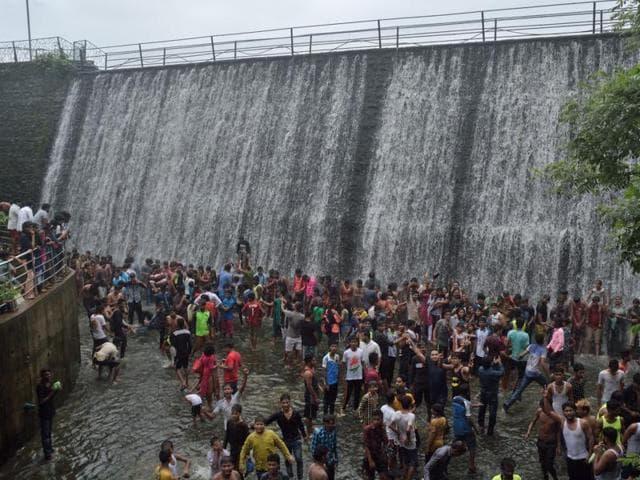 People enjoy the waterfall at Powai Garden in Mumbai on Sunday.