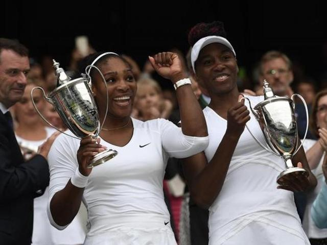 USA's Serena Williams and Venus Williams celebrate winning their womens doubles final against Hungary's Timea Babos and Kazakhstan's Yaroslava Shvedova with the trophies.