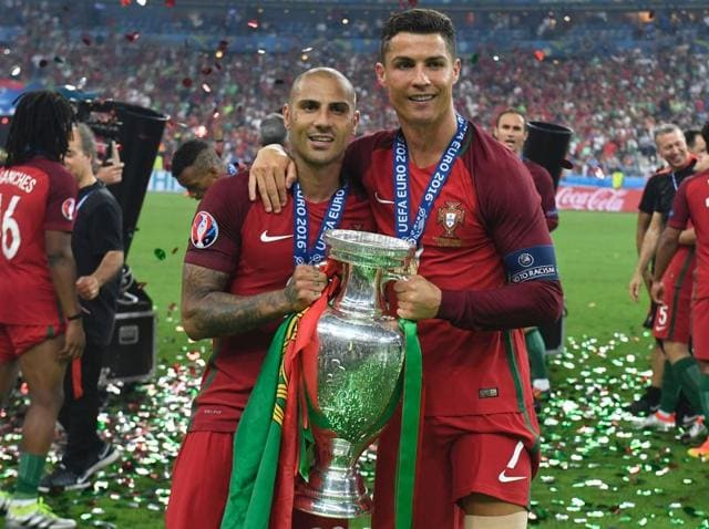Portugal's Cristiano Ronaldo (R) and forward Ricardo Quaresma hold the trophy after Portugal beat France in the Euro 2016 final at the Stade de France in Paris on July 10, 2016.