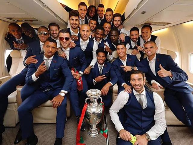 Portugal's national football team players posing with the trophy aboard the plane returning to Portugal.