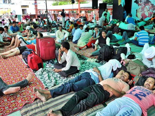 Amarnath Yatries sitting on a road as they waiting for their registration.(Photo by Nitin Kanotra / HIndustan Times)
