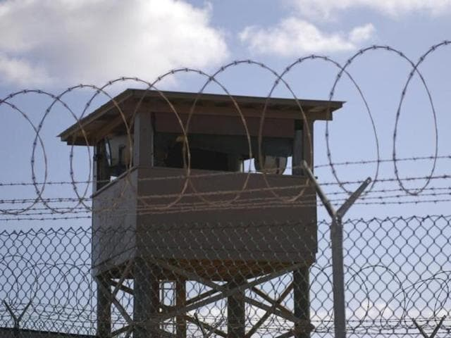 A soldier stands guard in a tower overlooking Camp Delta at Guantanamo Bay naval base.