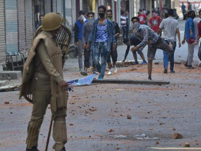 Protesters throw stones at policemen in Srinagar. Security forces were trying to contain protests by Kashmiris angry after several people were killed in weekend demonstrations, as youths defied a curfew to rally in the streets against the killing of militant Burhan Wani.