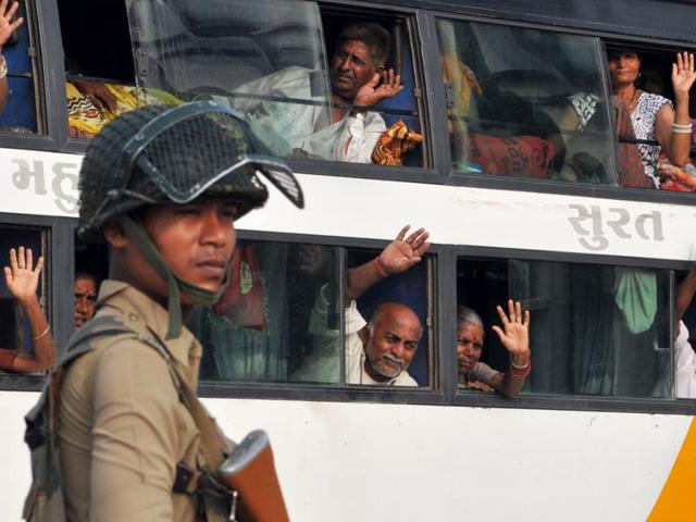Security forces stand guard as a bus takes Amarnath cave pilgrims from the base camp, in Jammu on Monday.