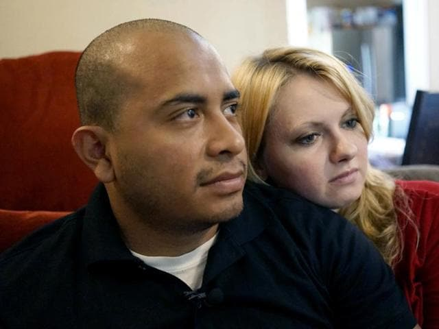 Dallas Police Department Officer Jorge Barrientos, left, is pictured recovering at his home with his girlfriend, Bethany Knutson, Sunday, July 10, 2016, in Dallas. Barrientos was shot in the hand and struck by shrapnel when a gunman attacked officers at a protest against police brutality July 7, 2016.