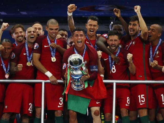 Portugal's Cristiano Ronaldo celebrates with team mates and the trophy after winning Euro 2016 against France at Stade de France in Paris.