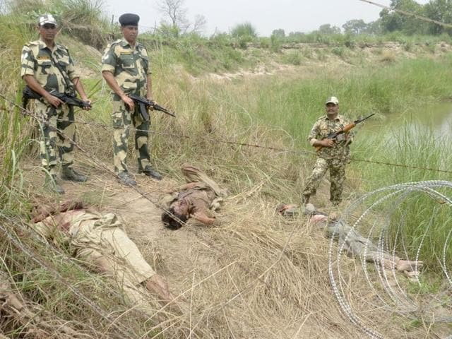 BSF jawans near the bodies of Pakistani intruders in Ajnala near Indo-Pak border on Tuesday.