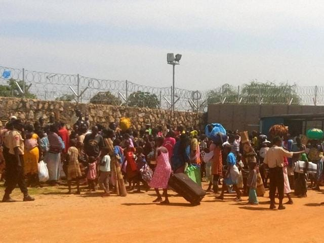 People with their luggage gather outside the gate seeking shelter in the WFP compound in Juba.