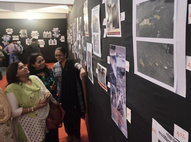 People attend a photo exhibition showcasing the plight of roads riddled with potholes in Mumbai.