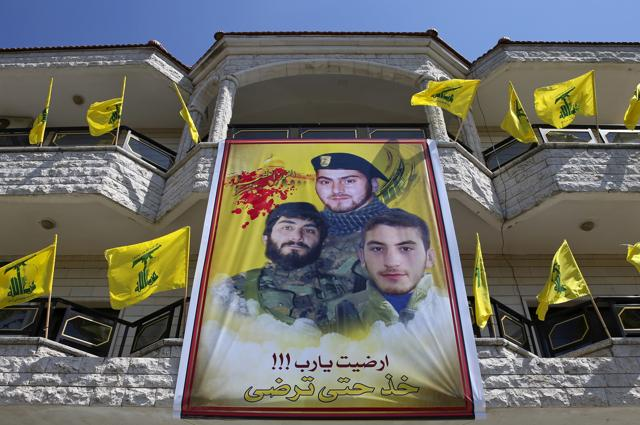 In this photo, a huge poster showing portraits of Mahdi Daqiq (top) who was killed in August 2006 and his nephew Mohammed Daqiq (right), who was killed in July  2006 during fighting with Israel in the 2006 war and his nephew Ali Daqiq who was killed in Khalsa, southern Aleppo, in June, 2016. Arabic on the poster reads