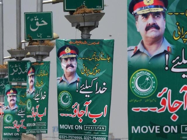Pakistani commuters drive past posters of army chief Gen Raheel Sharif in Peshawar on Tuesday. Posters begging Pakistan's powerful army chief to launch a coup appeared in major cities, including the capital Islamabad, overnight, raising eyebrows in a country that has been ruled by the military for more than half its history.