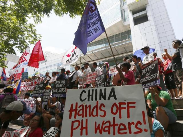 Protesters display placards during a rally outside of the Chinese Consulate in Makati city east of Manila, Philippines, hours before the Hague-based UN international arbitration tribunal is to announce its ruling on South China Sea on Tuesday.