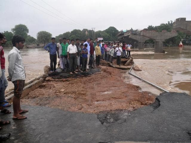 People wade through a flooded road in Vidisha on Tuesday.