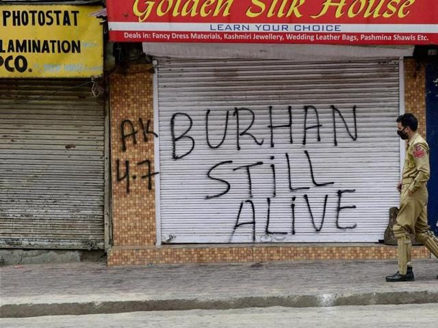 A policeman walks past closed shops in Srinagar on Monday. Clashes over Burhan Wani's death have hit life in Jammu and Kashmir.