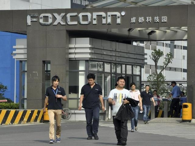 Workers walk out of the entrance to a Foxconn factory in Chengdu, Sichuan province, China.
