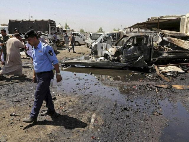 Civilians and security personnel gather at the scene of a deadly suicide car bombing at an outdoor market in a Shia-dominated al-Rashidiya district.