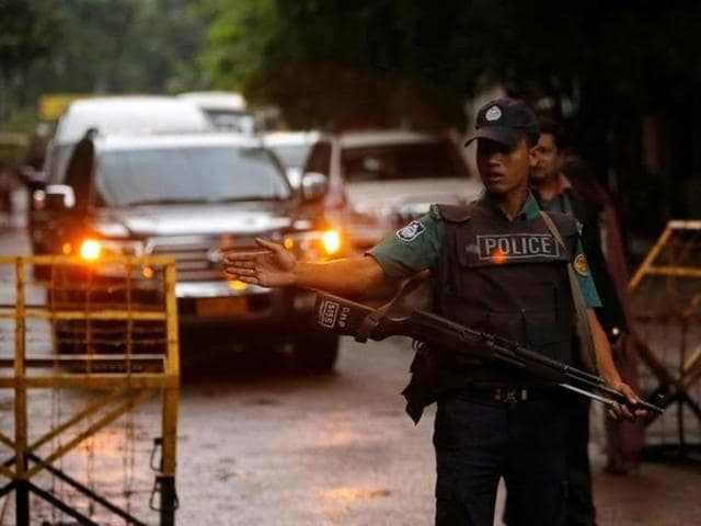 A policeman keep watch as a Japanese convoy with relatives of victims of the attack on Holey Artisan Bakery visited the site in Dhaka.