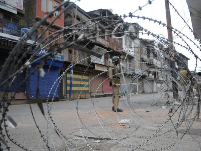 Policeman stands guard near a barbed wire during curfew in Srinagar.