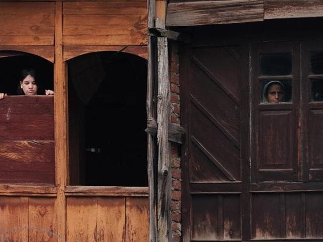 Kashmiris look out of the windows of a house in Srinagar on Wednesday. Police and government officials say that banning mobile and internet services is a 'violence control measure'.
