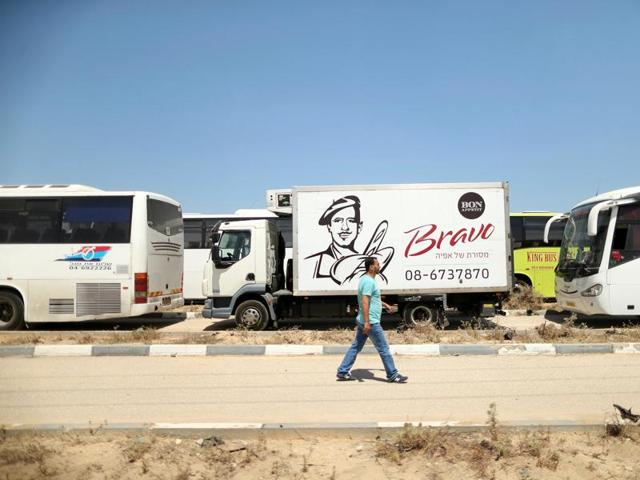 A Palestinian man walks past vehicles upon arrival at Erez crossing between Israel and northern Gaza Strip.