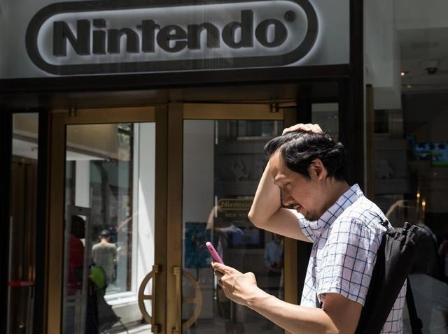 A man plays Pokemon Go on his smartphone outside of Nintendo's flagship store in New York City.
