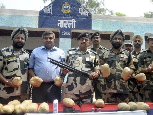 BSF officials display the shot gun, ammunition and 21 packets of contraband recovered near Narli village on Wednesday.
