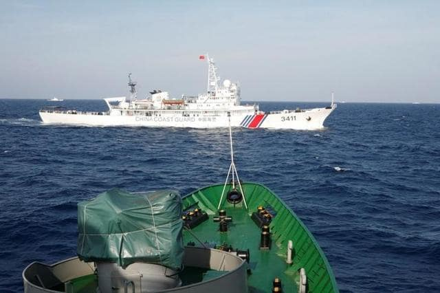 A ship (top) of the Chinese Coast Guard is seen near a ship of the Vietnam Marine Guard in the South China Sea, about 210 km (130 miles) off shore of Vietnam May 14, 2014.