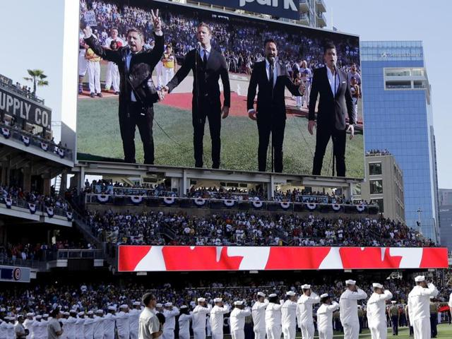 The Tenors, shown on the scoreboard, caused a stir with Remigio Pereira's actions while singing