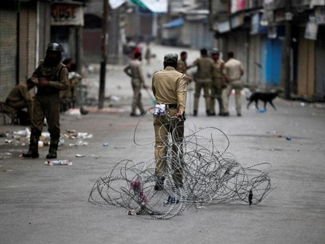 A policeman pulls concertina wire to lay a barricade on a road during a curfew in Srinagar.