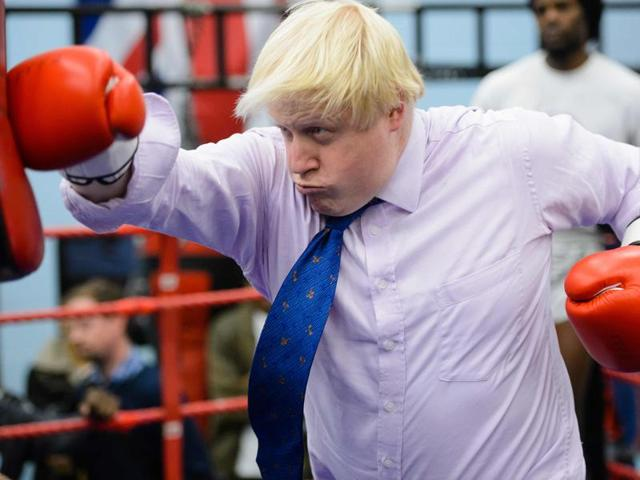 Boris Johnson, when he was the London Mayor, boxes with a trainer during his visit to Fight for Peace Academy in North Woolwich, London in October 2014.