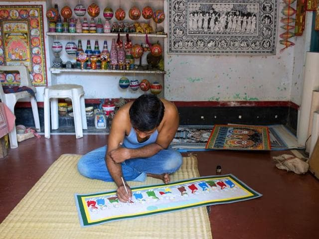 An artist displays a Patachitra scroll in Raghurajpur, Odisha