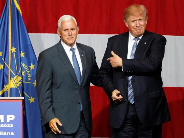 Republican presidential candidate Donald Trump (R) and Indiana Governor Mike Pence (L) wave to the crowd before addressing the crowd during a campaign stop at the Grand Park Events Center in Westfield.