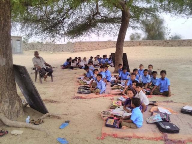 Students study under a tree at a Barmer school.