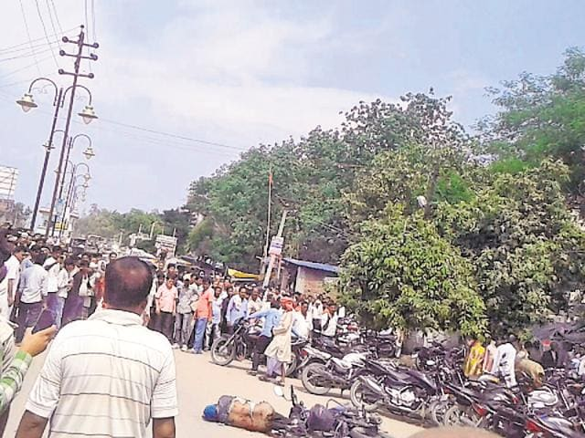 Crowd gathers outside the Sasaram civil court after the bomb explosion as the victim lies dead near the motorcycle.