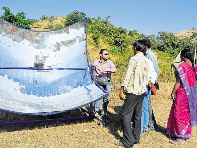 Mihir Mathur demonstrating solar parabolic cookers to villagers in Maharashtra.