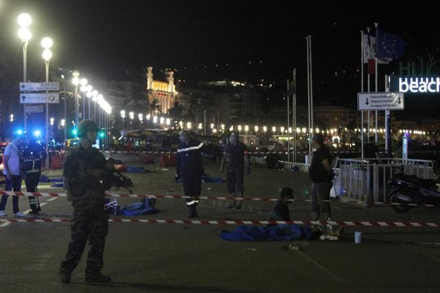 Soldiers, police officers and firefighters walk near dead bodies covered with a blue sheets on the Promenade des Anglais seafront in the French Riviera town of Nice.