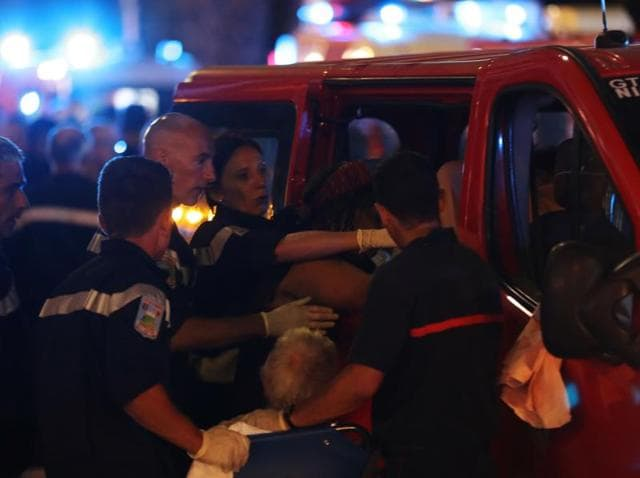 Rescue workers help injured people to get in an ambulance on July 15, 2016, after a truck drove into a crowd watching a fireworks display in the French Riviera town of Nice.