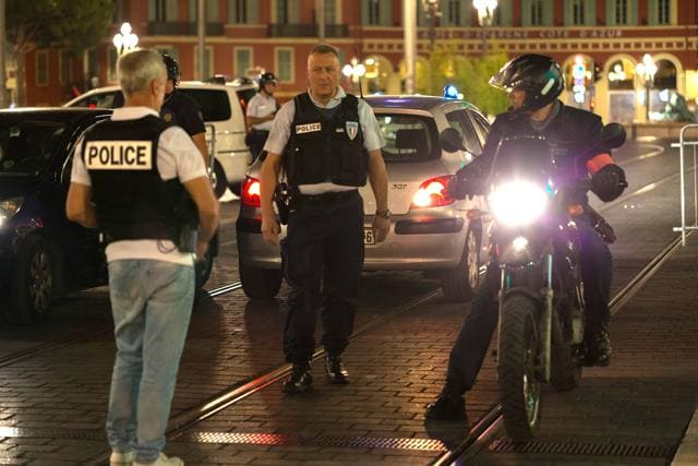 Police officers seal off the area of an attack after a truck drove on to the sidewalk and plowed through a crowd of in Nice last Friday.