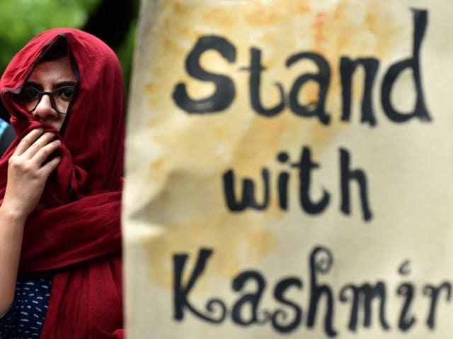 A Kashmiri woman looks out from a window of her home during a curfew, Srinagar, July 12.