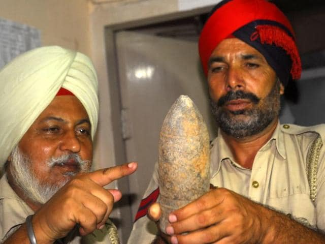 Cops with one of the shells found in cantonment area of Amritsar on Saturday.