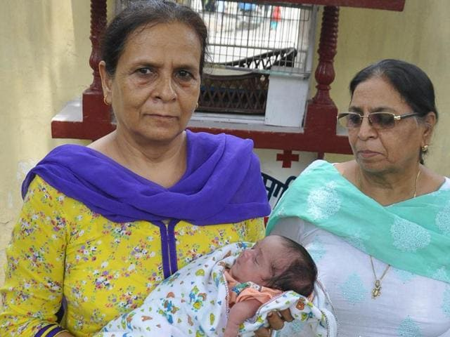 District administration officials with the abandoned baby girl Pangoora in Amritsar on Friday.