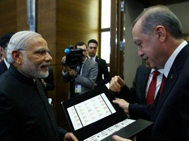 Turkish President Recep Tayyip Erdogan, right, presents a photo album to Prime Minister Narendra Modi at the end of the G-20 Summit in Antalya, Turkey.