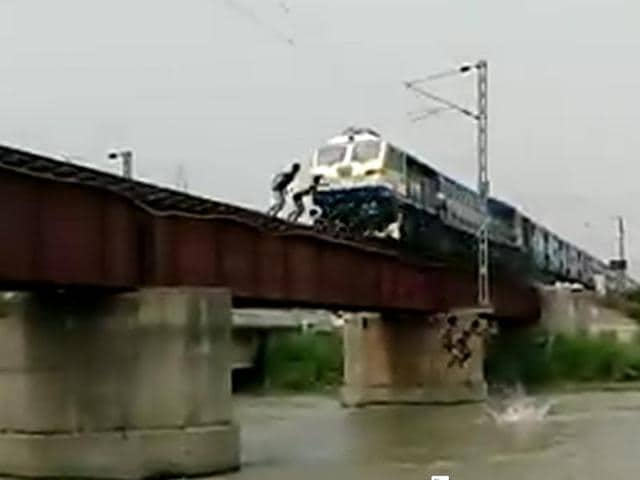 A video grab  shows kids jumping off a railway overbridge moments before a speeding train crosses it in Ghaziabad. The video went viral, prompting authorities to act.