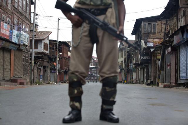 A soldier stands guard during curfew in Srinagar.