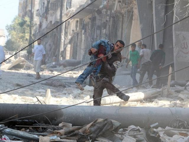 A man carries an injured man amid rubble of damaged buildings after an airstrike on Aleppo's rebel held al-Fardous district in Syria on Saturday.