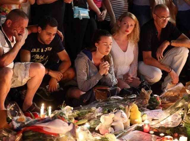 People gather at a makeshift memorial to pay tribute to the victims of an attack in the French Riviera city of Nice.