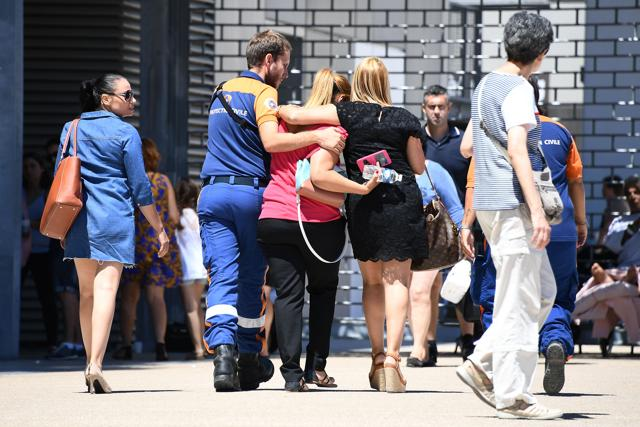 An agent of the Civil Protection (Protection Civile) comforts a woman outside Pasteur hospital in the French riviera town of Nice on Saturday, after the July 14 truck attack that killed 84 people in Nice on France's national holiday.